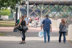 Donkere gevilde vrouw met twee zakken die een skateboard berijden stock afbeeldingen