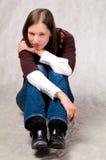 Donkere haired meisjeszitting met rechte benen stock afbeelding
