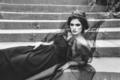 Donkere het liggen koningin in sluier op de stappen van foto van het paleis zwart-Wit Stock Fotografie