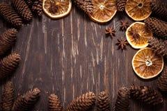 Donkere houten achtergrond met kegels, steranijsplant, droge sinaasappel met mede Royalty-vrije Stock Afbeeldingen