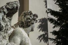 Donkere kant van een standbeeld van de steenengel dichtbij de muurschaduwen Stock Afbeeldingen
