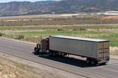 Donkere Klassieke semi vrachtwagen en aanhangwagen op de weg met aardmening Stock Foto