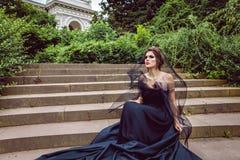 Donkere koningin in sluier op de stappen van paleis Stock Foto