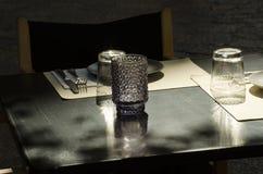 Donkere lijst openluchtdiekoffie, met toestellen en schotels met een glaskandelaar wordt gediend in het centrum royalty-vrije stock afbeelding