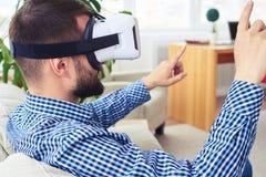 Donkere mens met baard die VR-glazen gebruiken terwijl het zitten op bank Stock Afbeeldingen