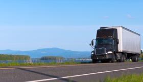 Donkere moderne vrachtwagen op achtergrond van de rivier en de bergen Stock Fotografie