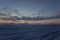 Donkere mooie hemel De Zon van de zonsondergang Snel drijvende wolken echte de winter ijzige zonsondergang op het gebied Stock Afbeeldingen