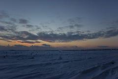 Donkere mooie hemel De Zon van de zonsondergang Snel drijvende wolken echte de winter ijzige zonsondergang op het gebied sihuette Stock Afbeelding