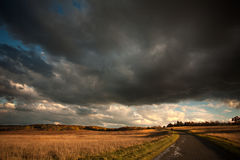 Donkere onweerswolken over bergweide bij zonsondergang Stock Foto