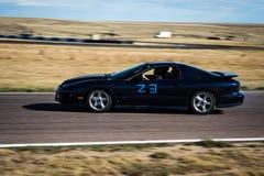 Donkere raceauto op spoor Stock Afbeeldingen