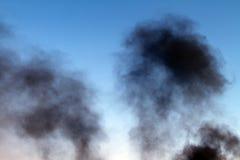 Donkere rookpijler op de blauwe hemelachtergrond royalty-vrije stock fotografie