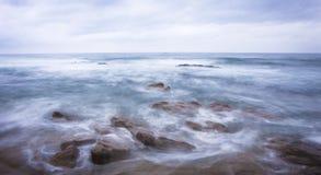 Donkere rotsen in een blauwe oceaan onder bewolkte hemel Royalty-vrije Stock Foto