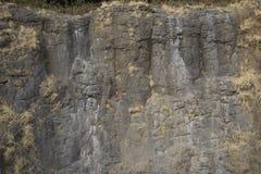 Donkere rotstextuur. Steenachtergrond Stock Afbeeldingen