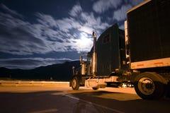 Donkere semi vrachtwagenadelborst in nachtlicht met dromerige wolken Royalty-vrije Stock Afbeelding