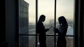 Donkere silhouetten van twee vrouwen tegen venster binnen bureau stock footage
