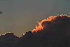 Donkere stormachtige wolken die de hemel behandelen door zonsondergang Stock Foto