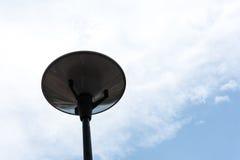 Donkere straatlantaarn die met bewolkte blauwe hemel wordt geïsoleerd stock afbeeldingen