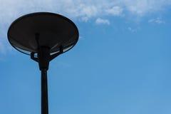 Donkere straatlantaarn die met bewolkte blauwe hemel wordt geïsoleerd royalty-vrije stock foto's