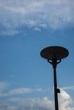 Donkere straatlantaarn die met bewolkte blauwe hemel wordt geïsoleerd royalty-vrije stock fotografie