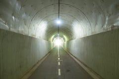Donkere tunnel met licht Stock Afbeeldingen