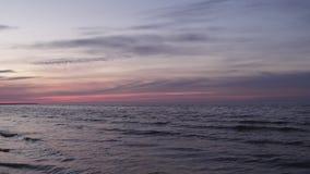 Donkere violette levendige kleuren tijdens een koude zonsondergang op de Oostzee in Letland stock footage