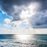 Donkere wolken en glanzende zon over het overzees stock afbeelding