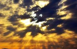 Donkere wolken en oranje zonstralen in de hemel Royalty-vrije Stock Afbeeldingen
