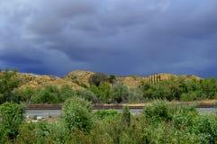 Donkere wolken en zon het shinning op landschap Stock Foto's