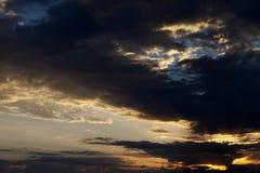 Donkere wolken en zonsopganghemel met zon Royalty-vrije Stock Foto