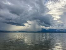 Donkere wolken met regenachtig in onweersdag op de meer en bergachtergrond Regendruppel slechts wat gebied stock foto's