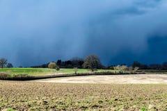Donkere wolken, onweren en zonneschijn met veranderlijk Brits weer in de vroege lente stock afbeelding