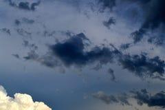 Donkere wolkenvlotter door de blauwe hemel Stock Foto's