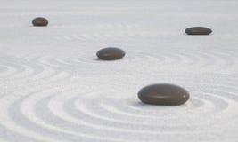Donkere Zen-stenen op breed zand Stock Afbeeldingen