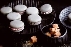 Donkere zwart-wit fotografie Grijze cakesmakarons op de donkere oppervlakte van de lijst, naast een lepel en suikerkom met Royalty-vrije Stock Fotografie
