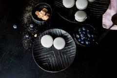 Donkere zwart-wit fotografie Grijze cakesmakarons op de donkere oppervlakte van de lijst, naast een lepel en suikerkom met Stock Fotografie