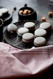Donkere zwart-wit fotografie Grijze cakesmakarons op de donkere oppervlakte van de lijst, naast een lepel en suikerkom met Stock Afbeelding