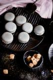 Donkere zwart-wit fotografie Grijze cakesmakarons op de donkere oppervlakte van de lijst, naast een lepel en suikerkom met Royalty-vrije Stock Foto's