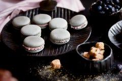 Donkere zwart-wit fotografie Grijze cakesmakarons op de donkere oppervlakte van de lijst, naast een lepel en suikerkom met Royalty-vrije Stock Afbeelding