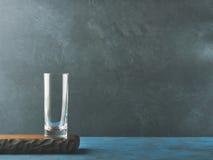 Donkere zwarte achtergrond met leeg glas op houten raad Stock Foto's