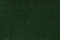 Donkergroene golvende achtergrond van een textielproduct Stof met de close-up van de vouwentextuur Stock Afbeelding
