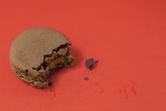 Donkergroene kleur van gebeten macaron op de houten lijst in rood Royalty-vrije Stock Foto's