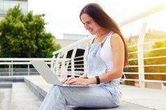 Donkerharige op de zonovergoten straat met laptop op haar knieën Royalty-vrije Stock Afbeeldingen