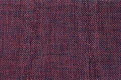 Donkerrode achtergrond van dichte geweven in zakken doende stof, close-up Structuur van de textielmacro Royalty-vrije Stock Afbeelding