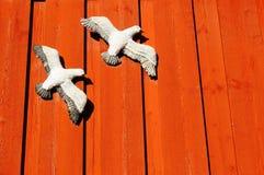 Donkerrode muren met beeldhouwwerk witte meeuwen Royalty-vrije Stock Fotografie