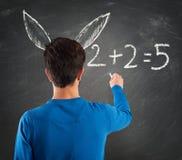Donkey student. Student with donkey ears writes math operation royalty free stock images
