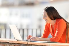 Données entrantes d'entrepreneur heureux dans un ordinateur portable sur le balcon photographie stock libre de droits