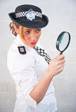 Donna 69 della polizia con la lente d'ingrandimento Immagine Stock
