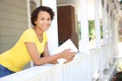 Donna abbastanza africana sul portico domestico immagine stock