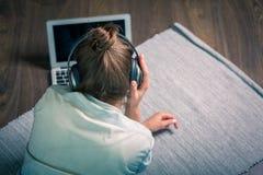 Donna abbastanza alla moda che ascolta la musica ed il web praticante il surfing Immagini Stock Libere da Diritti