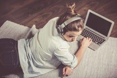 Donna abbastanza alla moda che ascolta la musica ed il web praticante il surfing Fotografia Stock